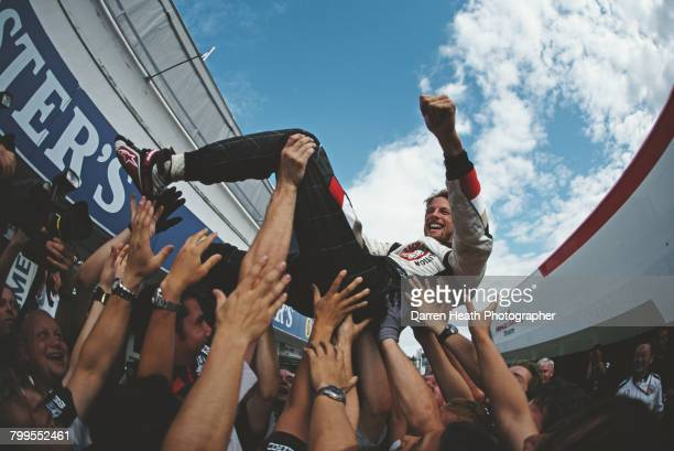 Jenson Button of Great Britain and driver of the Lucky Strike Honda Racing F1 Team Honda RA106 Honda RA806E V8 is lifted in the air by fellow team...