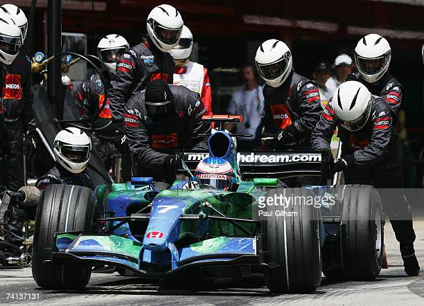 Jenson Button of Great Britain and Honda Racing is given a push by his team mechanics after a pitstop during the Spanish Formula One Grand Prix at...