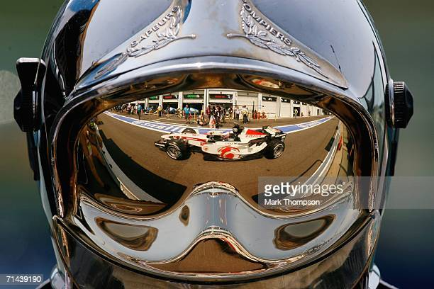 Jenson Button of Great Britain and Honda Racing is reflected in the helmet of a fire marshall during first practice for the French Formula One Grand...