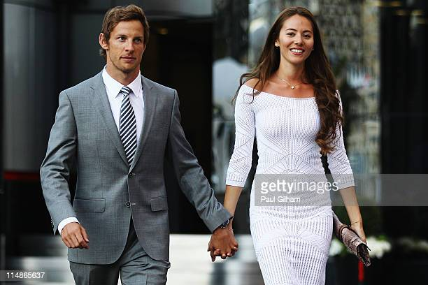 Jenson Button of Great Britain and McLaren and his girlfriend Jessica Michibata leave the paddock for the evening following previews to the Monaco...
