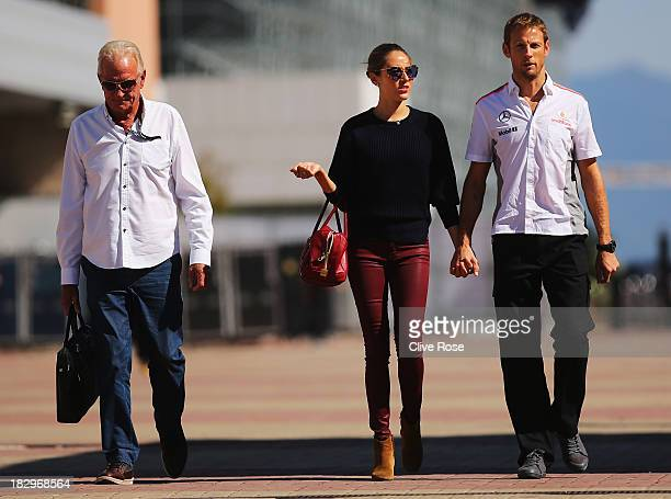 Jenson Button of Great Britain and McLaren and his girlfriend Jessica Michibata and his father John Button arrive in the paddock during previews for...