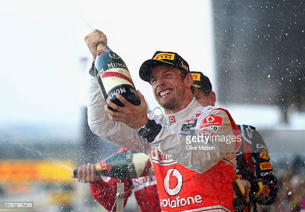 Jenson Button of Great Britain and McLaren celebrates on the podium after winning the Japanese Formula One Grand Prix at Suzuka Circuit on October 9,...