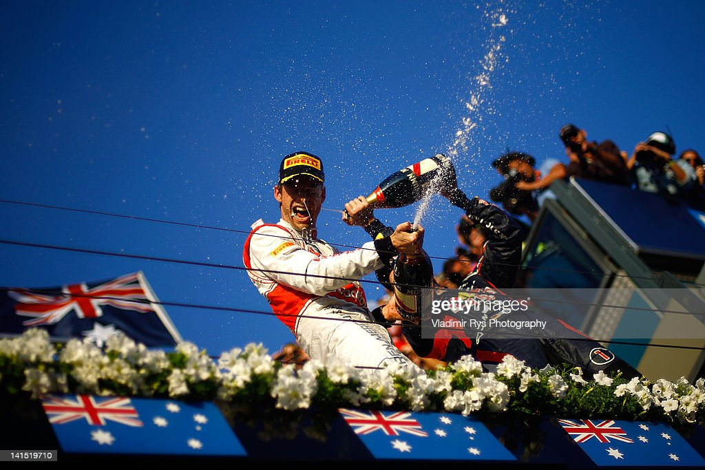 Jenson Button of Great Britain and McLaren (finishing first) celebrates on the podium with Sebastian Vettel of Germany and Red Bull Racing (finishing second) after the Formula One Grand Prix of Australia at Albert Park circuit on March 18, 2012 in Melbourne, Australia.