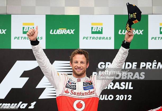 Jenson Button of Great Britain and McLaren celebrates on the podium after winning the Brazilian Formula One Grand Prix at the Autodromo Jose Carlos...