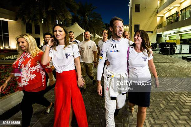 Jenson Button of Great Britain and Mclaren celebrates with his family and friends after retiring from his last F1 race during the Abu Dhabi Formula...