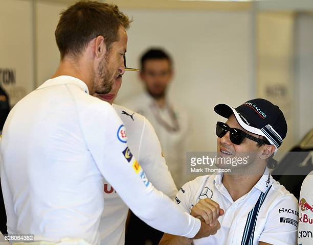 Jenson Button of Great Britain and McLaren Honda and Felipe Massa of Brazil and Williams shake hands before their final F1 race during the Abu Dhabi...
