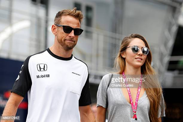 Jenson Button of Great Britain and McLaren Honda walks with his wife Jessica Button in the paddock during previews to the Formula One Grand Prix of...