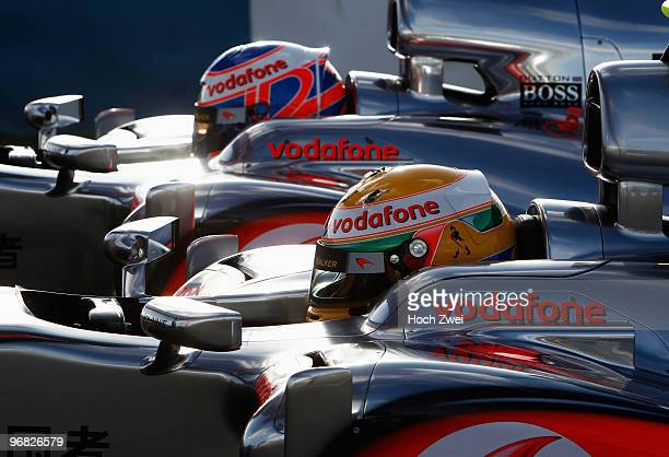 Jenson Button of Great Britain and McLaren Mercedes and Lewis Hamilton of Great Britain and McLaren Mercedes sit side by side in their cars during...