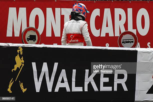 Jenson Button of Great Britain and McLaren Mercedes walks back to the pits after retiring early with an engine problem during the Monaco Formula One...
