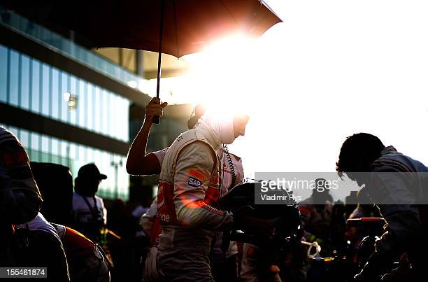 Jenson Button of Great Britain and McLaren prepares on the starting grid ahead of the Abu Dhabi Formula One Grand Prix at the Yas Marina Circuit on...