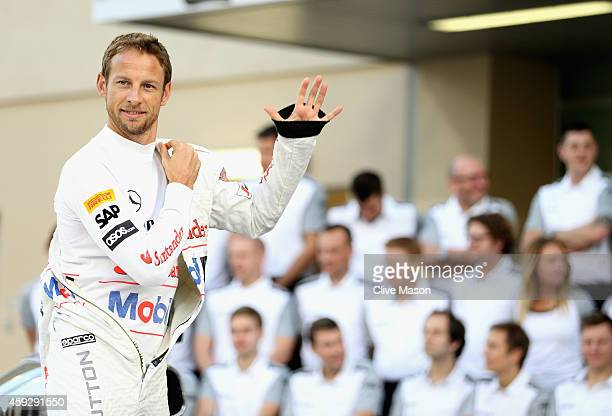 Jenson Button of Great Britain and McLaren waves as he takes his place for a team photograph during previews ahead of the Abu Dhabi Formula One Grand...