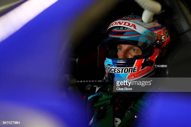 Jenson Button of Great Britain and Team Kunimitsu Honda Raybrig NSX-GT looks on in the pits during the Autobacs SuperGT series official test at the...