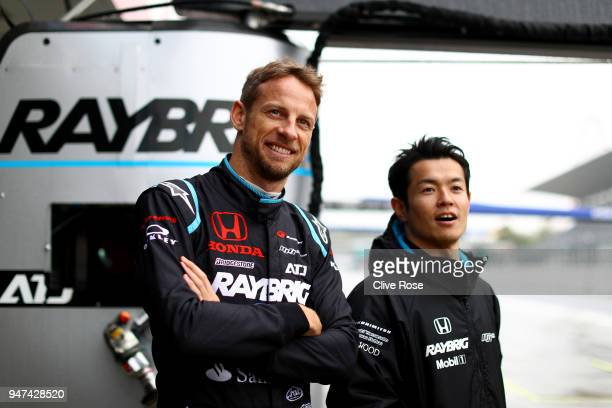 Jenson Button of Great Britain and teammate Naoki Yamamoto of Team Kunimitsu Honda Raybrig NSXGT look on together in the pits during the Autobacs...