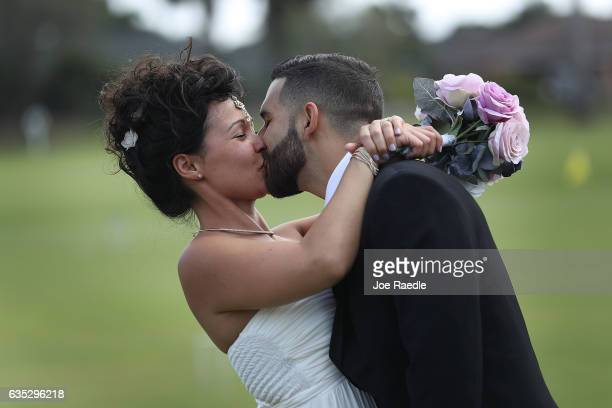 Jentue Pereira kisses her husband Diego Pereira after participating in a group Valentine's day wedding ceremony at the National Croquet Center on...