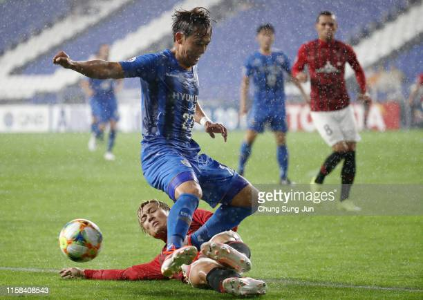 Jeong Dong-ho of Ulsan Hyundai is tackled by Ryosuke Yamanaka of Urawa Red Diamonds during the AFC Champions League round of 16 second leg match...