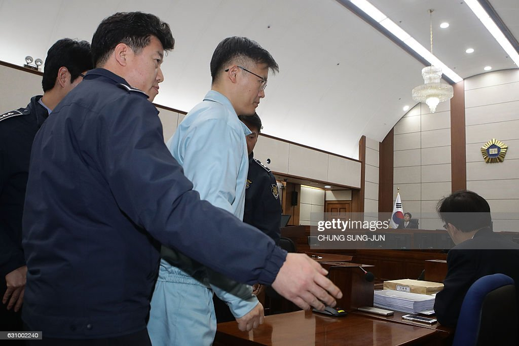 Jeong Ho-seong (C-light blue), former secretary for private presidential affairs, appears during the first day of his trial at the Seoul Central District Court in Seoul on January 5, 2017. Jeong is a key witness in South Korea's President Park Geun-hye's impeachment trial, which has led to the biggest political crisis for a generation. / AFP / POOL / Chung Sung-Jun
