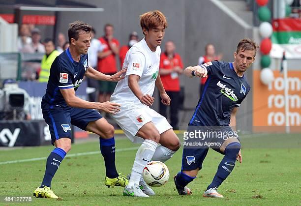 JeongHo Hong of Augsburg and Vladimir Darida and Peter Pekarik of Berlin fight for the ball during the Bundesliga soccer match between FC Augsburg...
