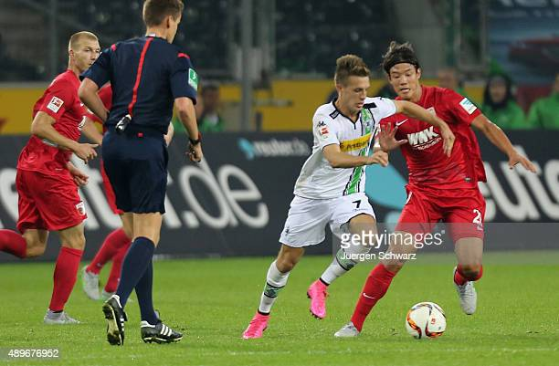 JeongHo Hong of Augsburg tackles Patrick Herrmann of Moenchengladbach during the Bundesliga match between Borussia Moenchengladbach and FC Augsburg...