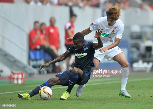 JeongHo Hong of FC Augsburg challenges Salomon Kalou of Hertha BSC during the Bundesliga match between FC Augsburg and Hertha BSC at WWKArena on...