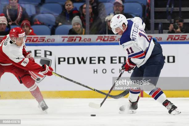 Jeppe Mogensen of Denmark defends as Casey Mittelstadt of United States moves the puck in the first period during the IIHF World Junior Championship...