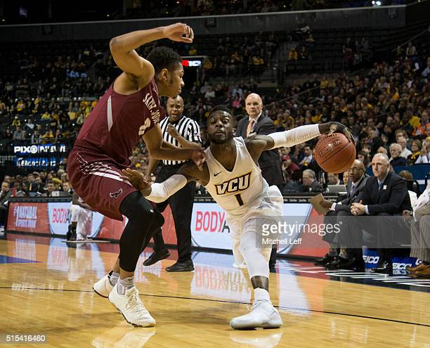 JeQuan Lewis of the Virginia Commonwealth Rams controls the ball against Lamarr Kimble of the Saint Joseph's Hawks in the championship game of the...