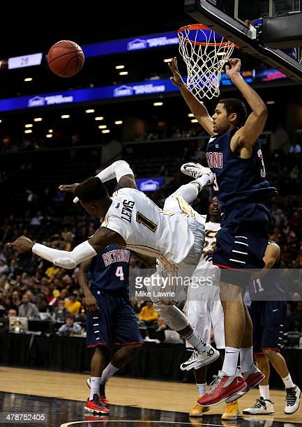 JeQuan Lewis of the Virginia Commonwealth Rams falls to the court after being fouled against Alonzo Nelson-Ododa of the Richmond Spiders in the...