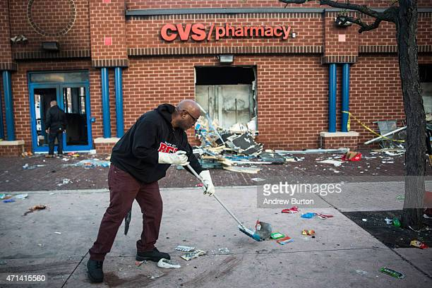 Jerald Miller helps clean up debris from a CVS pharmacy that was set on fire yesterday during rioting after the funeral of Freddie Gray, on April 28,...