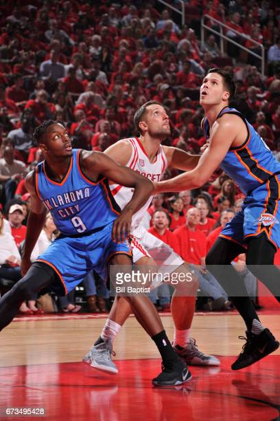 Jerami Grant and Doug McDermott of the Oklahoma City Thunder box out Ryan Anderson of the Houston Rockets in Game Five of the Western Conference...