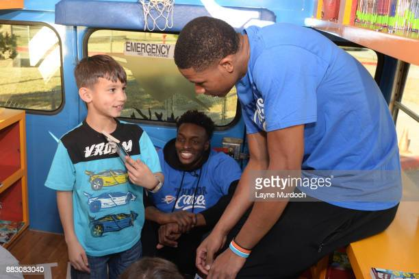Jerami Grant and PJ Dozier of the Oklahoma City Thunder help students select a free book on the Rolling Thunder Book Bus in conjunction with the NBA...