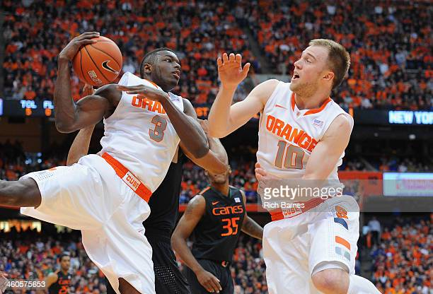 Jerami Grant and Trevor Cooney of the Syracuse Orange battle for a rebound against the Miami Hurricanes during the first half at the Carrier Dome on...