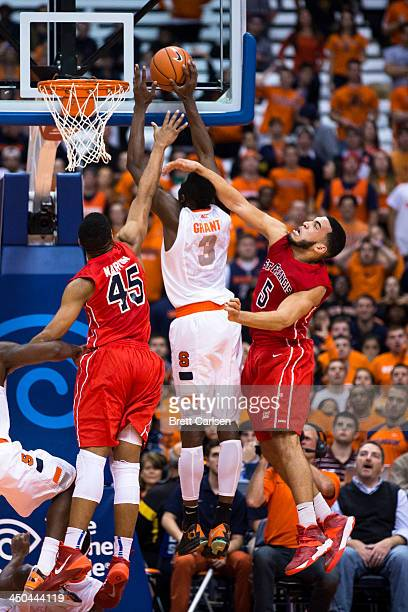 Jerami Grant of Syracuse Orange puts in a field goal in the second half while defenders Wayne Martin and Jalen Cannon of St Francis Terriers reach in...