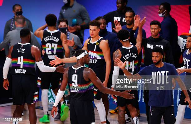 Jerami Grant of the Denver Nuggets and Paul Millsap of the Denver Nuggets celebrate their win with teammates against the Los Angeles Lakers in Game...