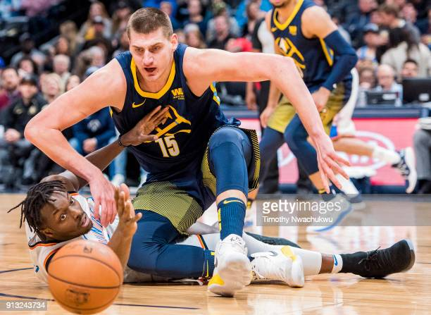 Jerami Grant of the Oklahoma City Thunder and Nikola Jokic of the Denver Nuggets look at a loose ball at Pepsi Center on February 1 2018 in Denver...