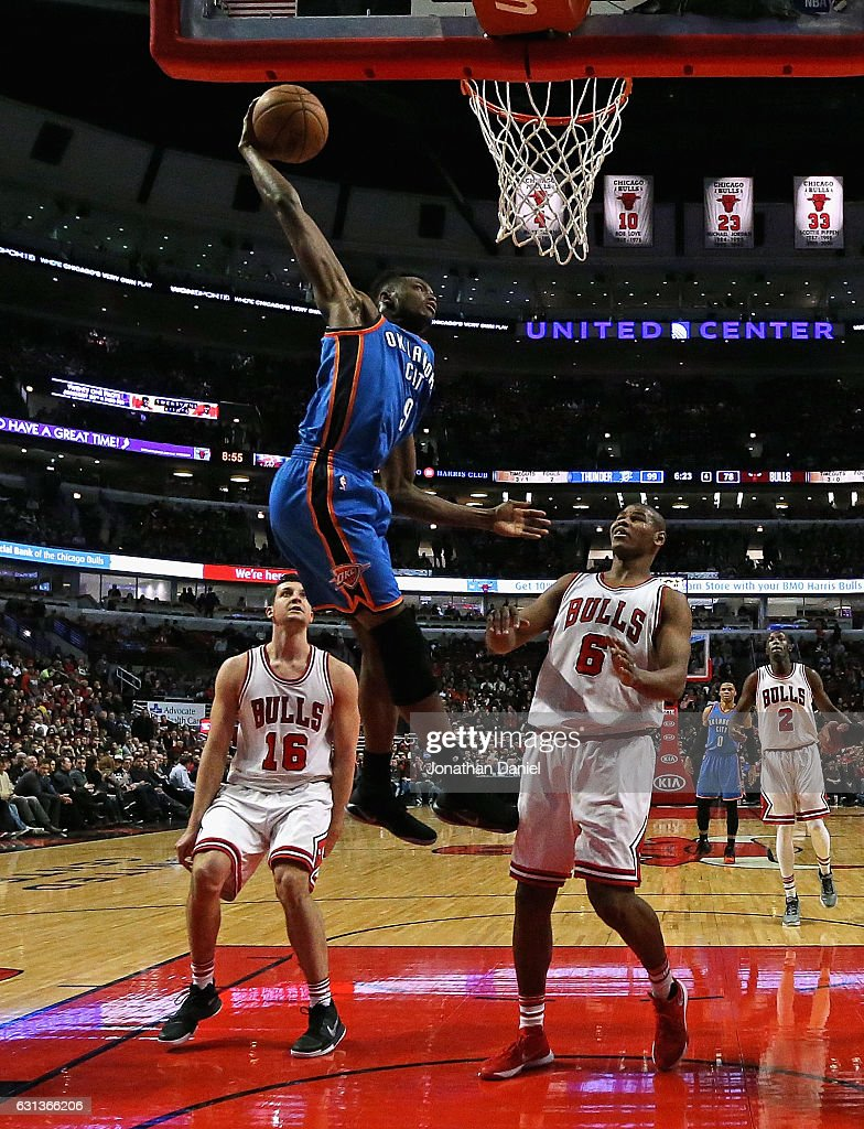Jerami Grant #9 of the Oklahoma City Thunder dunks over Paul Zipser #16 and Cristiano Felicio #6 of the Chicago Bulls at the United Center on January 9, 2017 in Chicago, Illinois. The Thunder defeated the Bulls 109-94.