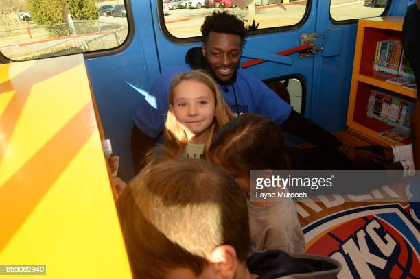 Jerami Grant of the Oklahoma City Thunder helps students select a free book on the Rolling Thunder Book Bus in conjunction with the NBA Read to...
