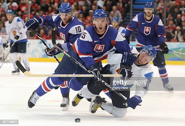 Jere Lehtinen of Finland fights for the puck against Jozef Stumpel of Slovakia during the ice hockey men's bronze medal game between Finland and...