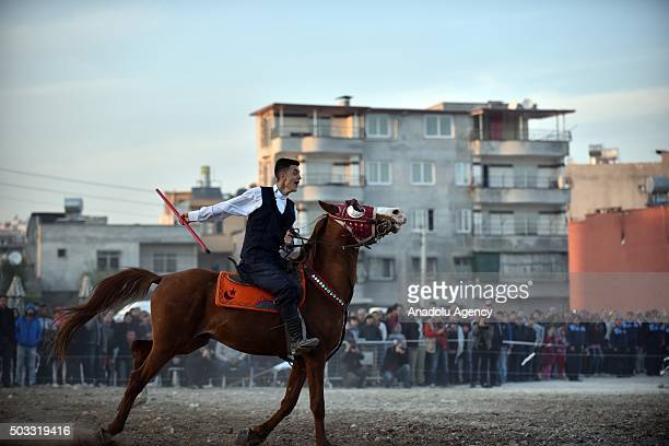 Jereed player from Erzurum Farm Sport Club, who is riding a horse, throws a wooden javelin as he performs a ceremonial jereed game during a ceremony...