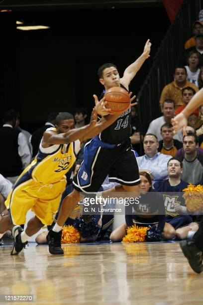 Jerel McNeal of Marquette and Duke's David McClure dive for a loose ball during the CBE Classic championship game between Marquette and Duke at...