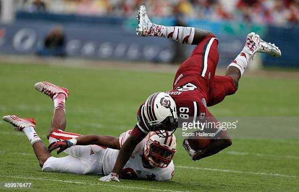 Jerell Adams of the South Carolina Gamecocks gets tackled by Sojourn Shelton of the Wisconsin Badgers during the first half of the Capital One Bowl...