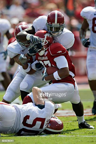 Jerell Norton of the Arkansas Razorbacks is tackled by the defense during a game against the Alabama Crimson Tide at Donald W Reynolds Stadium on...