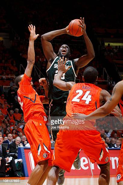 Jereme Richmond and Mike Davis of the Illinois Fighting Illini defend a shot by Draymond Green of the Michigan State Spartans at Assembly Hall on...