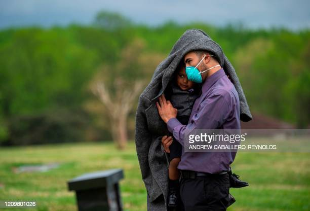 Jeremiah Flowers, wearing a mask for protection, looks on holding his son Nolan James Flowers as the casket of his grandfather, the pastor of the...