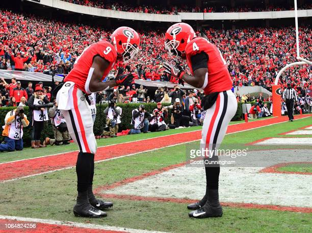 Jeremiah Holloman of the Georgia Bulldogs celebrates with Mecole Hardman after scoring a second quarter touchdown against the Georgia Tech Yellow...