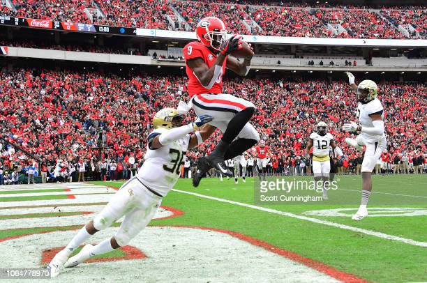 Jeremiah Holloman of the Georgia Bulldogs makes a catch for a second quarter touchdown against Malik Rivera of the Georgia Tech Yellow Jackets on...