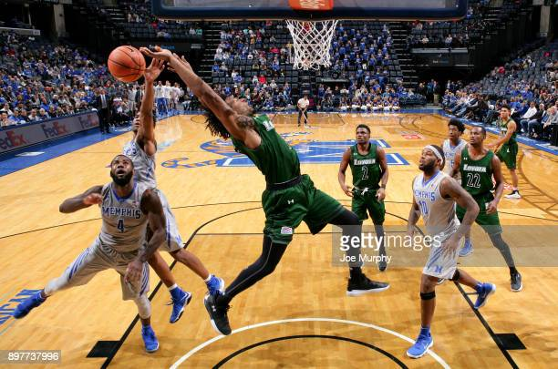 Jeremiah Martin and Raynere Thornton of the Memphis Tigers jump for a rebound against Kavaughn Scott of the LoyolaMaryland Greyhounds on December 23...