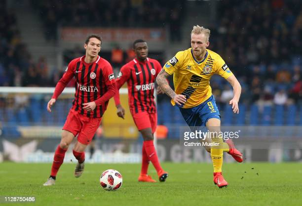 Jeremias Lorch and Agyemang Diawusie of SV Wehen Wiesbaden and Philipp Hofmann of Eintracht Braunschweig battle for the ball during the 3 Liga match...