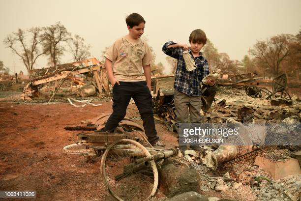 Jeremie and and Jacob Saylors look at religious statues they found in the burned remains of their home in Paradise California on November 18 2018 His...