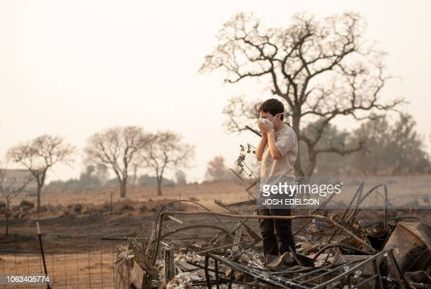 Jeremie Saylors adjusts his face mask while searching through the burned remains of his home in Paradise California on November 18 2018 His family...