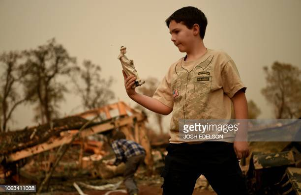 Jeremie Saylors looks at religious statues he found in the burned remains of his home in Paradise California on November 18 2018 His family lost a...