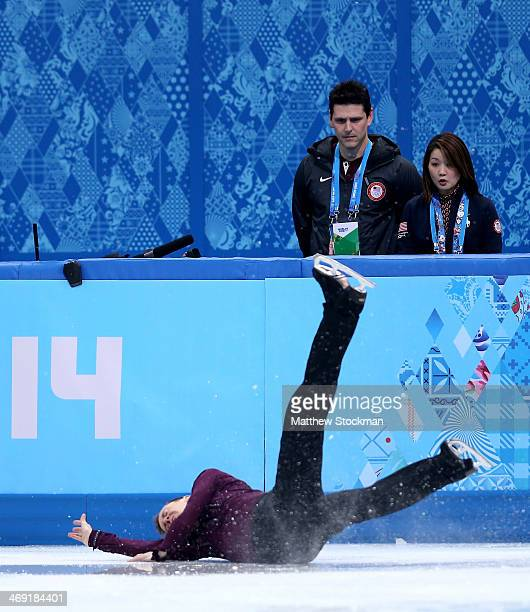 Jeremy Abbott of the United States falls in front of his coaches Yuka Sato and Jason Dungjen while competing during the Men's Figure Skating Short...